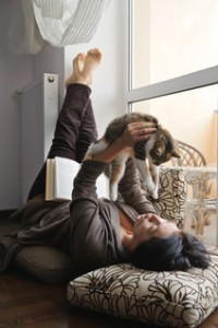 Woman playing with a kitten at the window in her apartment